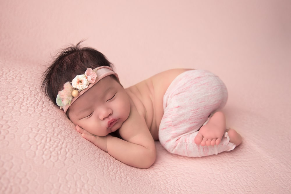 picture of adorable baby newborn girl posing on pink material while crossing legs and wearing flower crown