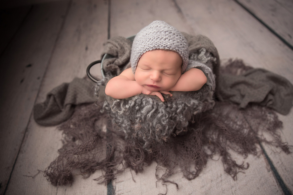 cute little newborn baby boy posing with gray knit cap while covered with blankets