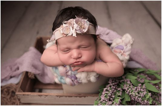beautiful baby girl surrounded by flowers and wearing flower crown for photo shoot during newborn photo shoot