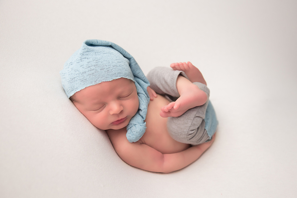 adorable baby boy wearing knit cap and crossing legs for joanna andres newborn photo shoot