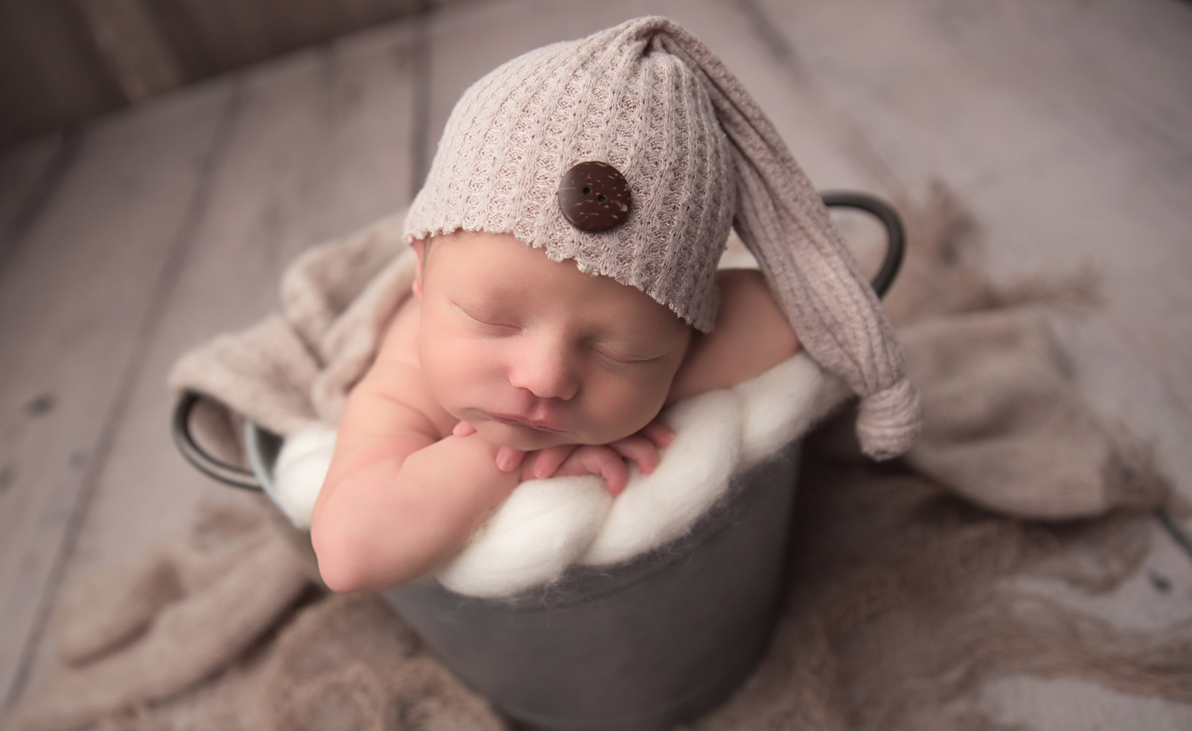 cute little newborn boy posing for photo shoot by joanna andres and wearing a knit cap