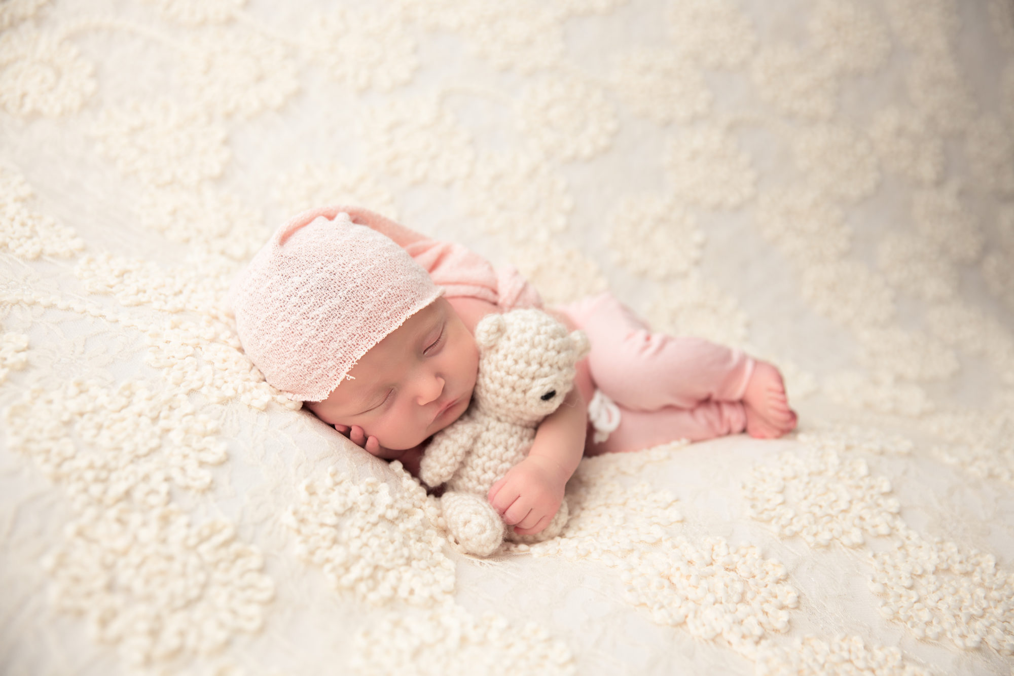 cute little newborn girl hugging teddy bear during photo shoot in columbus ohio